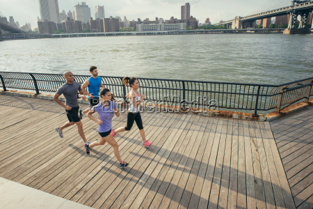 four adult runners running along riverside