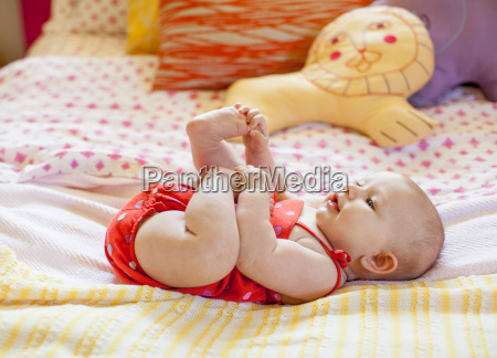 baby girl playing with feet on