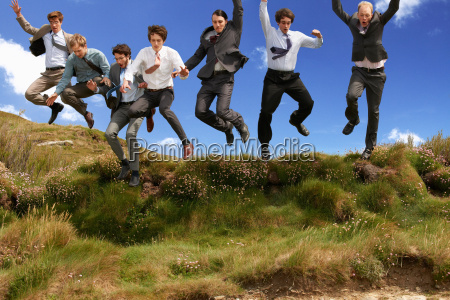 businessmen jumping for joy outdoors