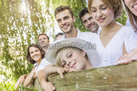 group of people standing behind fence
