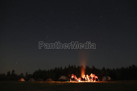 group of campers sitting around campfire