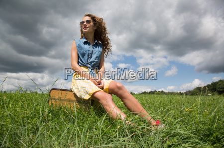 teenage girl sitting on suitcase in