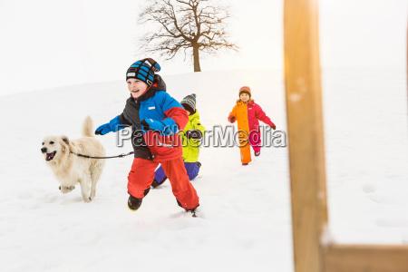 three children running in snow with