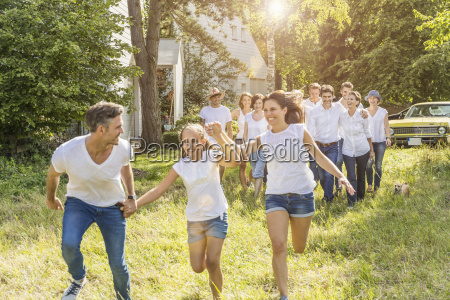 group of people running through forest