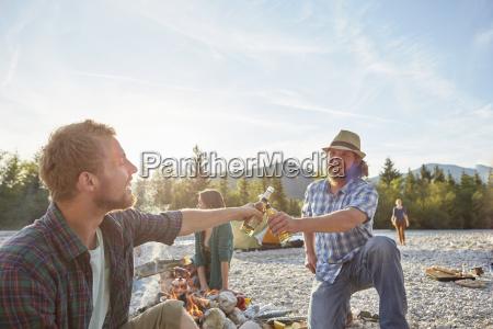 adult men sitting around campfire making