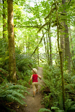 young boy walking along forest path