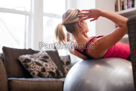 mid adult woman performing sit ups