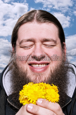 happy bearded man with yellow flowers