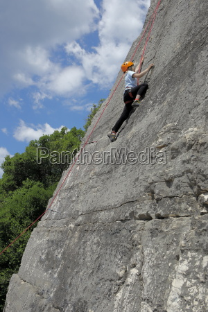 girl climbs on limestone wall