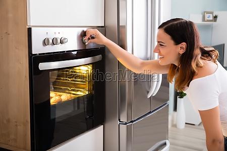 mulher que usa o forno de