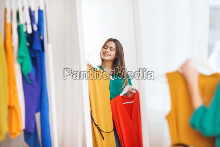 mulher feliz escolhendo roupas em casa