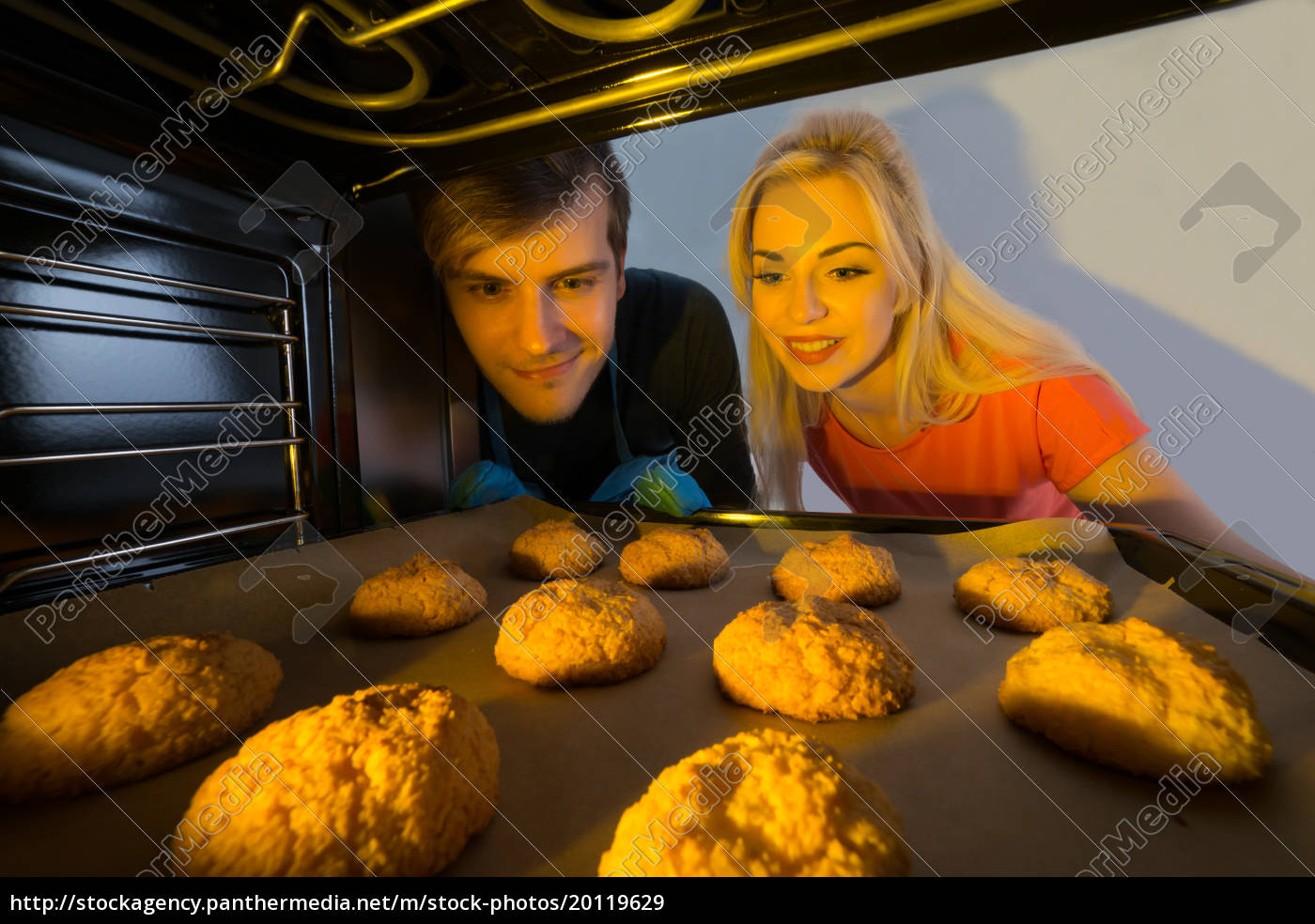 couple, looking, at, tray, of, cookies - 20119629
