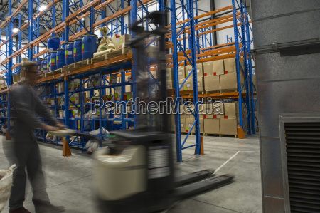 warehouseman in storehouse working with pallet