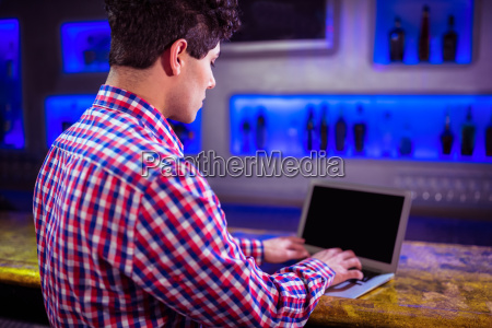 man using laptop at bar counter