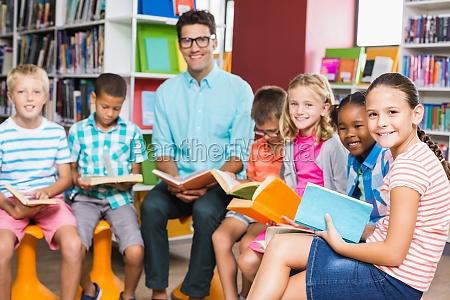 professor e criancas lendo livro na