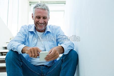 happy mature man using smartphone at