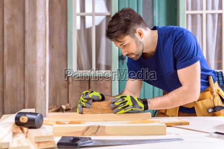 vista lateral do carpinteiro em luvas