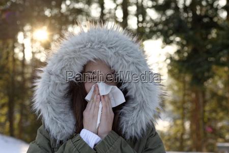teenage girl wearing hooded jacket blowing