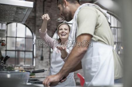 pares felizes que cozinham junto na