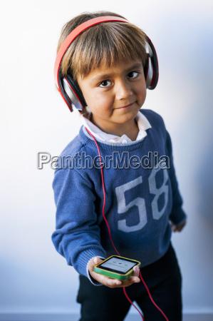 rapaz pequeno que escuta a musica