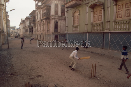children play cricket in the street