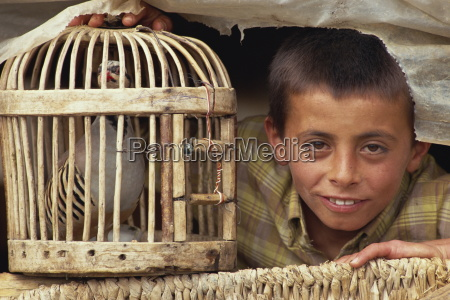 gypsy boy and caged bird near