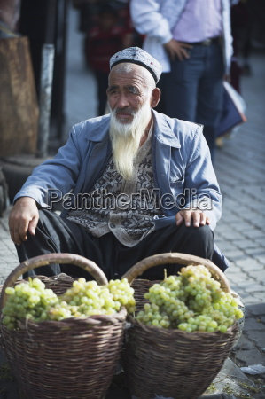 bearded man selling grapes at the