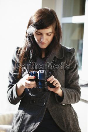 mulher nova que olha sua camera