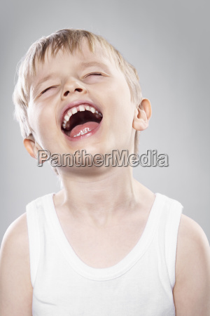 laughing boy agianst grey background close