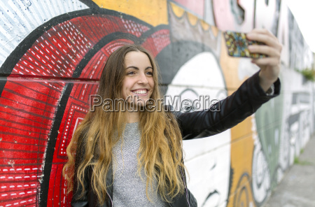 sorrindo menina adolescente levando um selfie