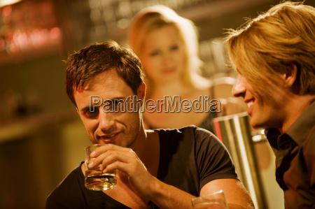 dois homens no bar bebendo