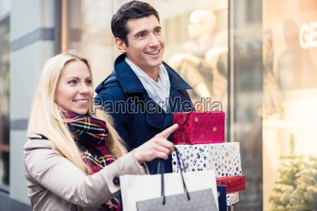 casal na vitrine fazendo compras de