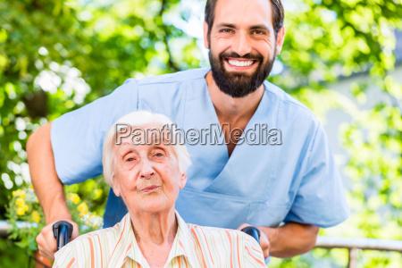 enfermeira geriatrica empurrando senhora senior na