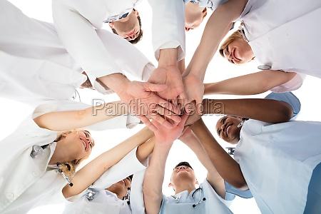 smiling medical team stacking hands