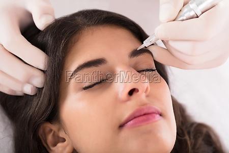 cosmetologista aplicando permanente make up em