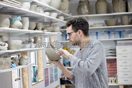 a man inspecting a clay pot