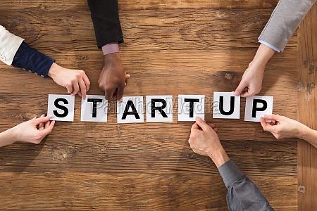 businesspeople hands arranging start up word