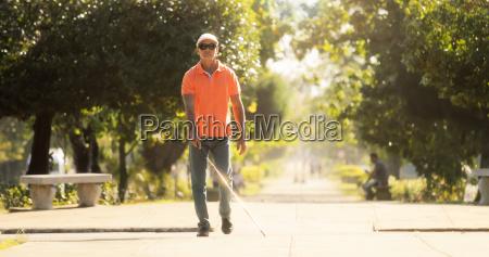 homem cego cruzando a rua e