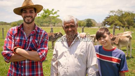 three generations family portrait of farmers