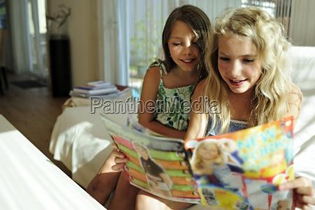 duas meninas que leem o compartimento