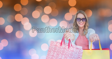 happy woman showing shopping bags over
