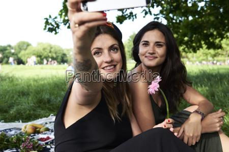 friends taking smartphone selfies in the