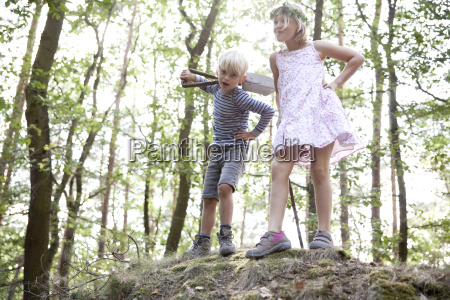 boy and girl standing in forest