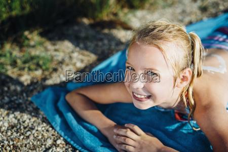 portrait of smiling blond girl lying