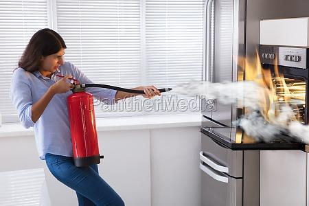 mulher que usa o extintor de