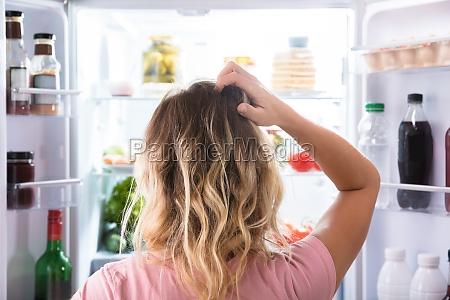mulher confusa que olha no refrigerador