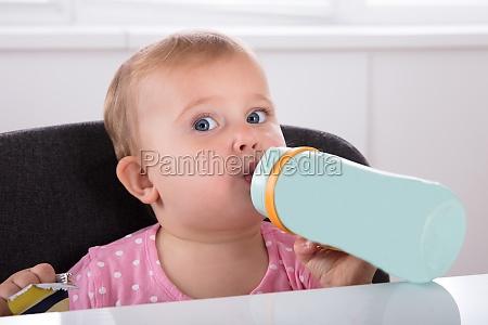 menina bebendo agua da garrafa