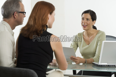 businesswoman talking to clients at desk