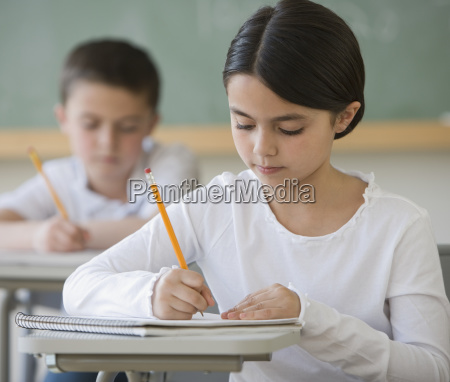 girl writing at desk in classroom