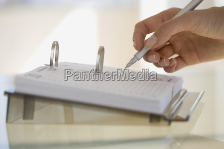 woman writing on desk calendar